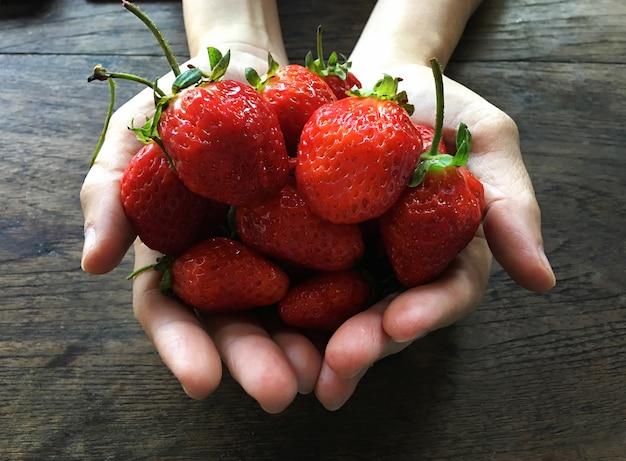 新鮮なイチゴの背景。女の子、手ざわり