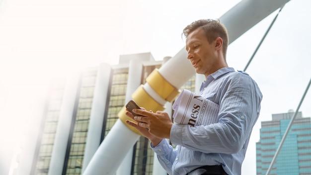最新のニュースを読む。屋外に立っている間、新聞を読んで自信を持った若い男