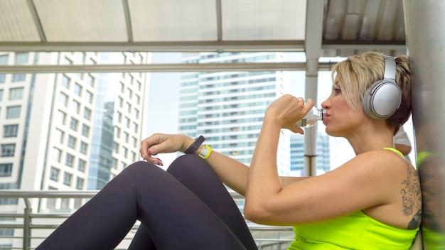 スポーツウェアの競技者ランナーは、座ってリラックスして、インスピレーションを得ています。