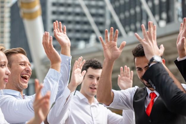 若いビジネスマンのグループは、目標の達成のために手を上げる