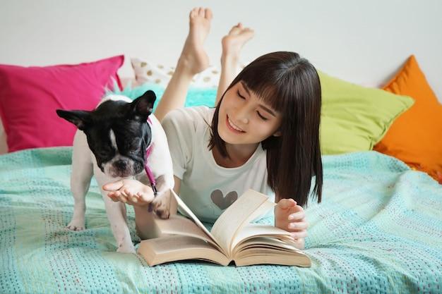 アジアの若い女性の肖像画は犬と遊ぶ