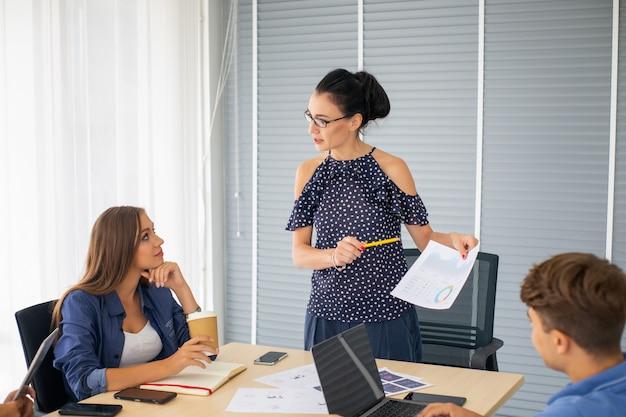 スタートアップビジネスオフィスで働き、机の上の書類で会議を行う創造的なビジネス人々