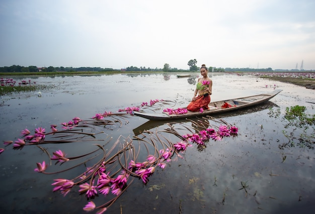 湖でボートに座ってロータスを保持している女性