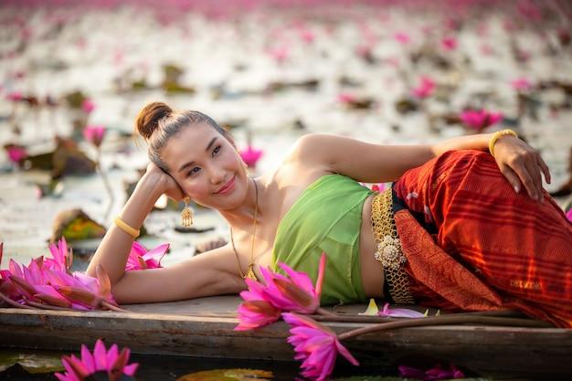 湖でボートにピンクロータスで横になっている若い女性の側面図