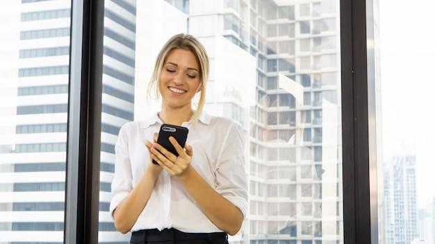 オフィスで携帯電話を保持している美しい実業家の肖像画