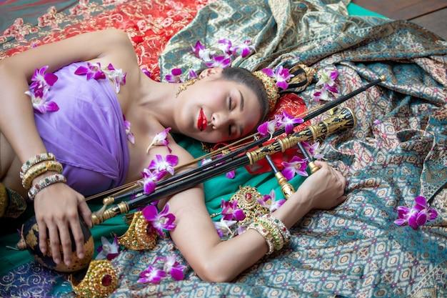 眠っている伝統的な衣装の女性花で床に横たわっている女性