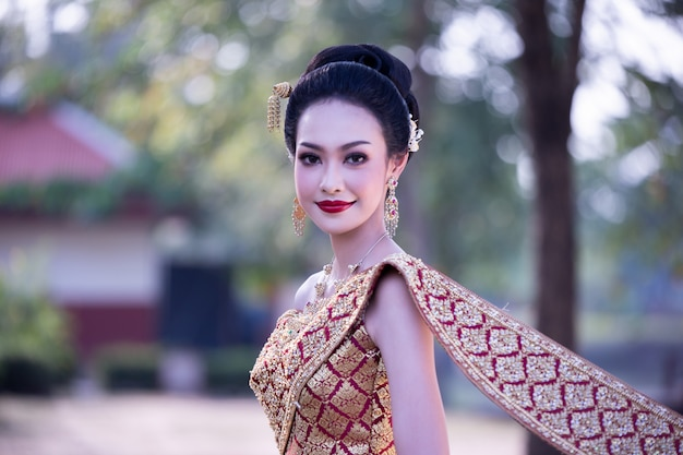 建物に対して立っているよそ見伝統的な服で笑顔の女性
