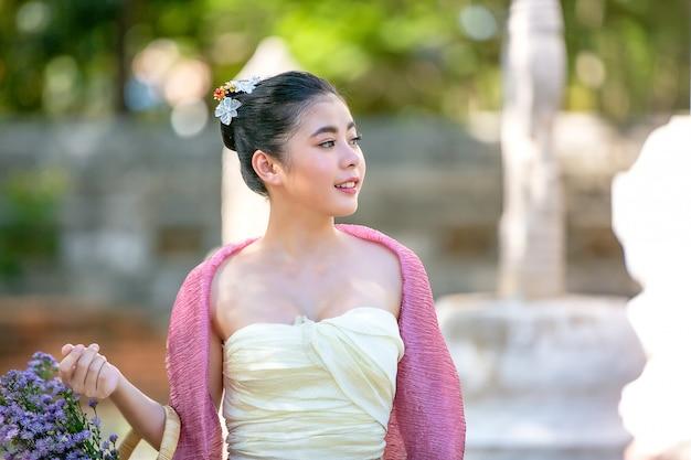 タイの寺院に対して立っているタイのランナーとシャンの伝統的な服のアジアの女性の肖像画