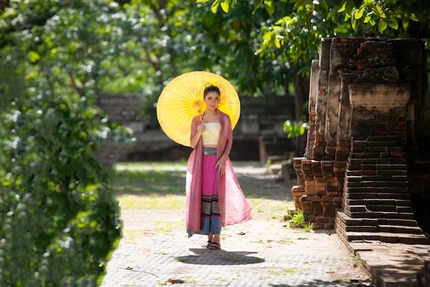植物に対して傘を保持しているタイのランナーとシャンの伝統的な服のアジアの女性