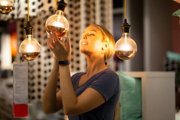 保持し、電球の光を見て女性が彼女の顔に反映