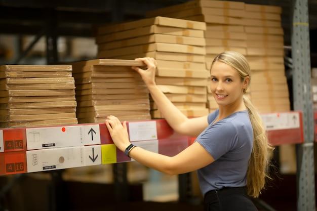 Жизнерадостный клиент женщины смотря вверх и вытягивая продукт на полке пока ходящ по магазинам в хозяйственном магазине