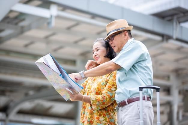 Двое азиатских стариков путешествуют с картой и багажом против здания
