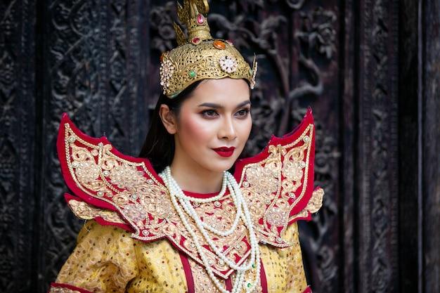 Женщины в традиционном костюме мандалая против деревянной двери