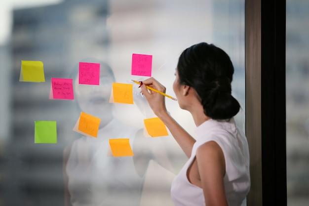 ビジネスの女性は、ガラス窓にメモ帳に書く