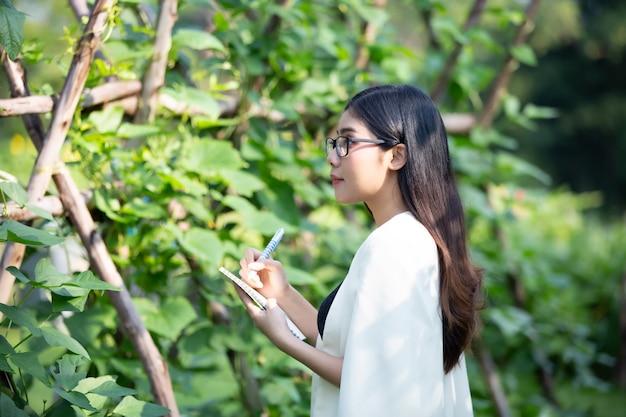 プランテーションでスモールビジネス農家の植物をチェックする女性の肖像画