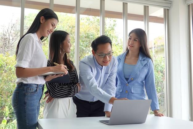 話しているとブレーンストーミングのカジュアルなスーツを持つアジアビジネス人々のグループ