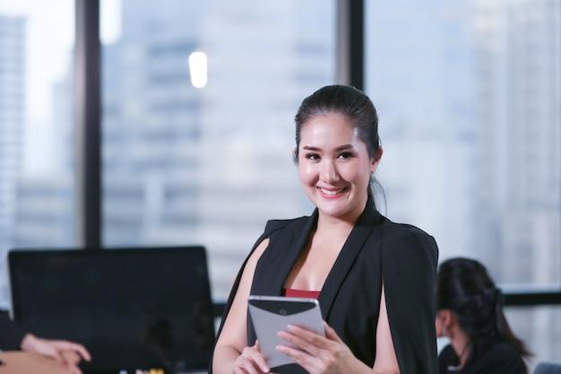オフィスに立っているタブレットを保持しているビジネス女性
