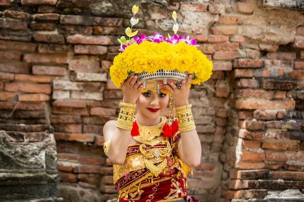 Портрет улыбающейся молодой женщины в балийской традиционной одежде, держащей букет цветов в храме