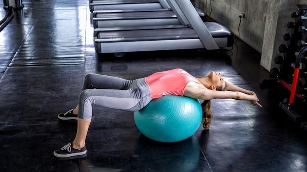 Женщины занимаются йогой и отдыхают в фитнес-зале