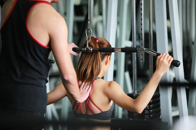 Женщина занимается тяжелой атлетикой с тренером