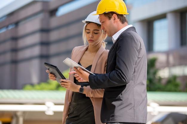 Два бизнесмена и женщины в защитных жилетах разговаривают и рукопожатие на строительной площадке
