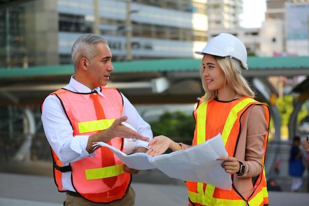 Строительные рабочие, глядя на чертежи на строительной площадке