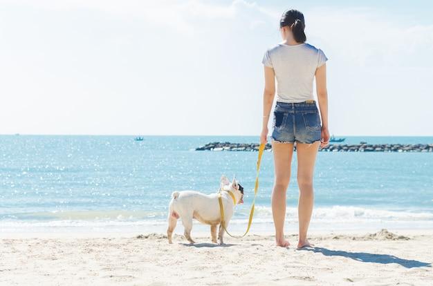 フレンチブルドッグと女性がビーチに立つ
