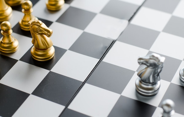 Серебряный и золотой рыцарь на шахматной доске. шахматные рыцари голова к голове.