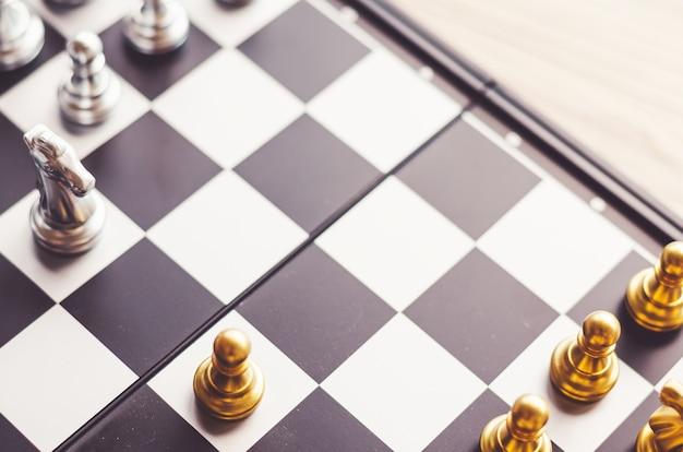 Серебряный и золотой рыцарь на шахматной доске. шахматные рыцари голова к голове. бизнес-концепция