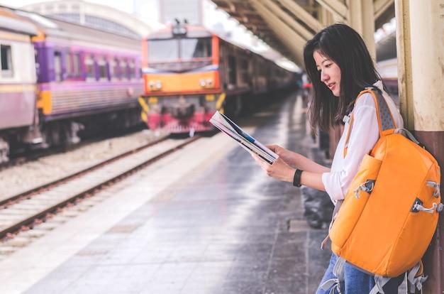 若い女性が駅に手をつないで地図を保持