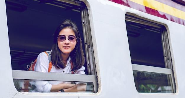 女の子は、バックパックを着て、列車を待っています。タイのバンコクを旅行しています。旅行コンセプト