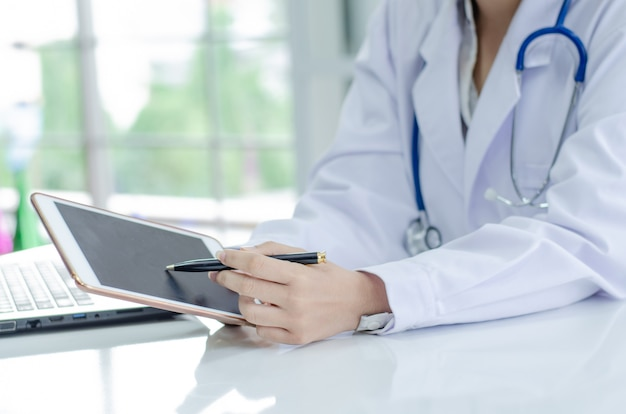 医者のラップトップコンピューターでの作業、書類に書いています。病院の背景