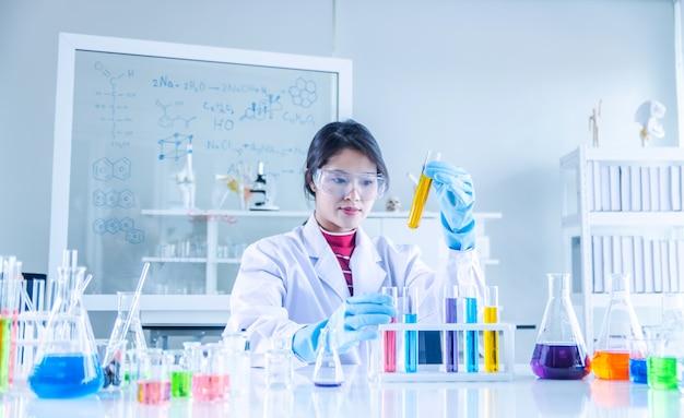 実験室でチューブを通して見る若い科学者