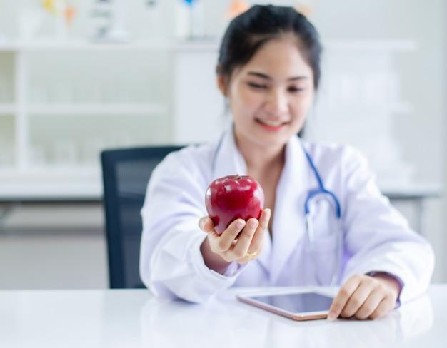 Женский доктор держа красное яблоко на руке
