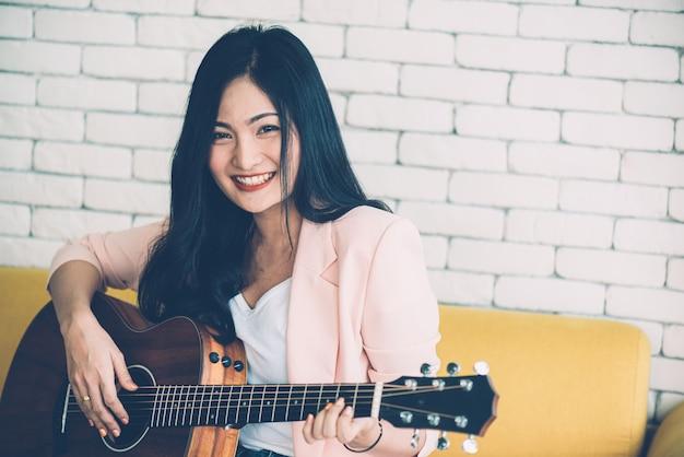 Женщина играет на гитаре на диване