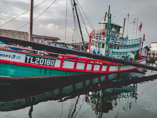 Фронт рыбацкой лодки в море. работающая рыбацкая лодка для продажи на берегу моря. рыбацкая лодка используется.