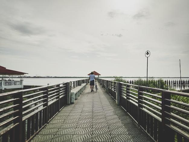 広大な海に通じる大きな橋の上の自転車サイクリングと男性