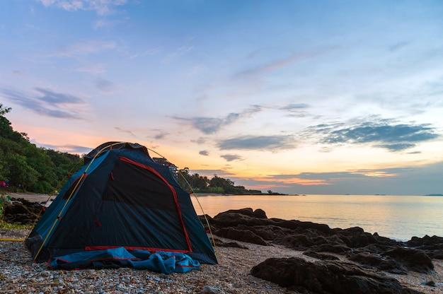 朝の岩とビーチでダークブルーのテント。