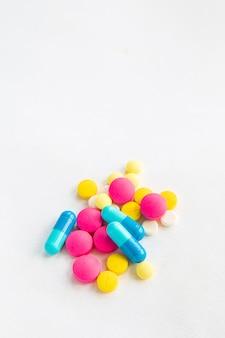 Закройте вверх по многоцветному лекарству и капсулам на белизне