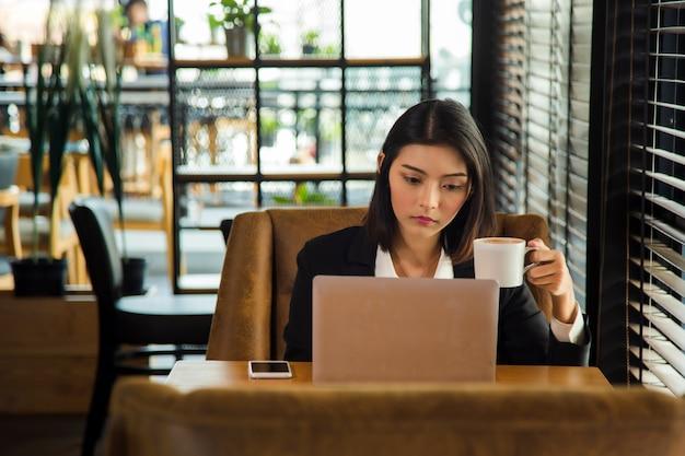 フォーマルスーツのアジアの女性はテーブルの次のウィンドウのラップトップで働いています。