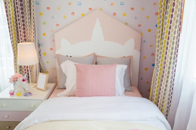 Красивая спальня для детей с розовой подушкой и розовой кроватью со сладкой стеной.