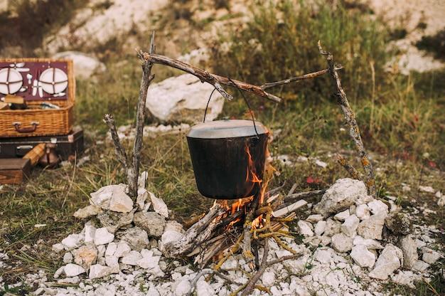 醸造された鍋にある森の中の火のイメージ