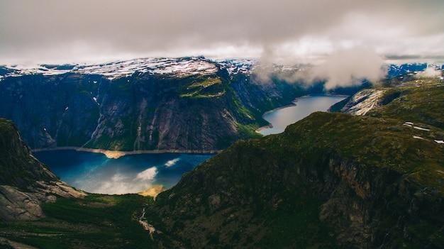 ノルウェーの有名な観光地であるトロルグンガ、湖と山々を持つトロール舌、ノルウェー、オッダの美しい夏の活気のある眺め。