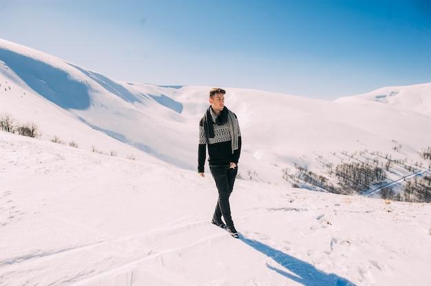 カリスマ的なハンサムな若い男は、雪山の背景にポーズをとる