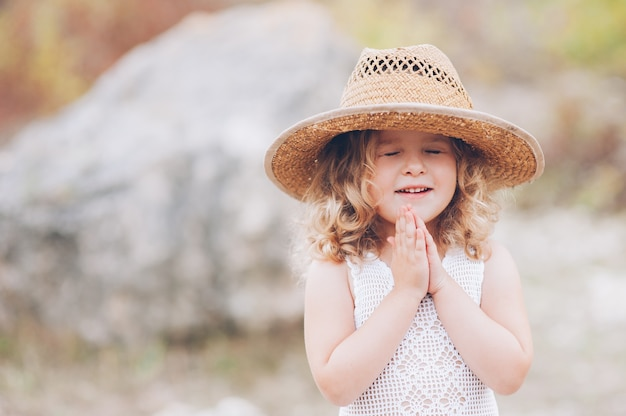 屋外で帽子を着ている幸せな少女