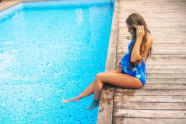 Красивая беременная женщина, расслабляющий возле голубой бассейн в купальнике