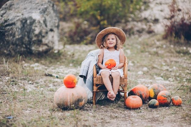 Очаровательная маленькая девочка в соломенной шляпе, плетеное кресло, тыквы, осень