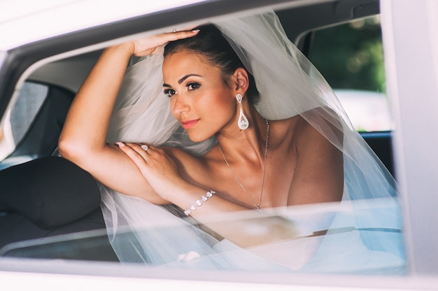 車内のレースのベール付きブライダルドレスの美人の花嫁。白いウェディングドレスの美しいモデルの女の子。自動車の女性の肖像画。髪型を持つ女性。かわいい女性屋外