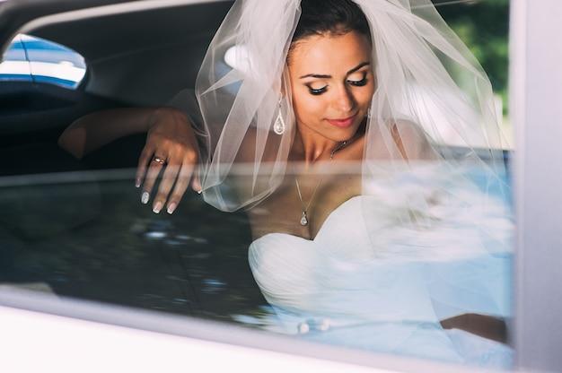 車のレースのベール付きのブライダルドレスの美人の花嫁