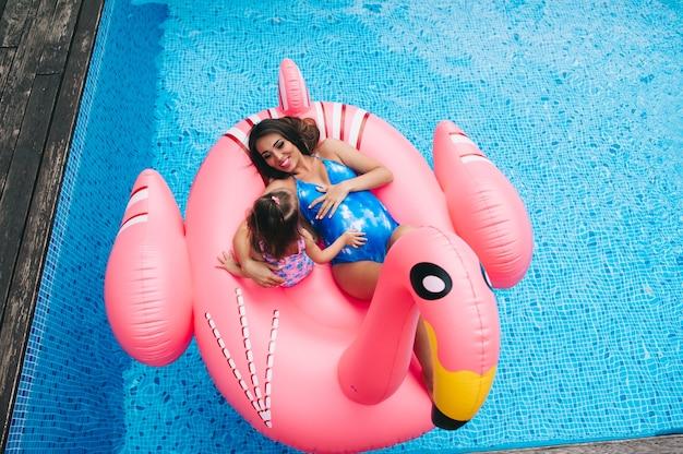 Беременная мать и ее дочь плавали на надувных розовых фламинго